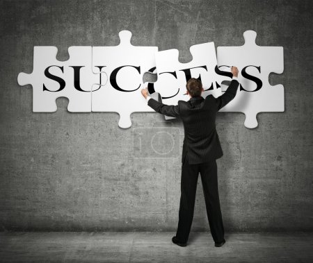 Photo for Businessman making a puzzle on the wall with the word Success - Royalty Free Image