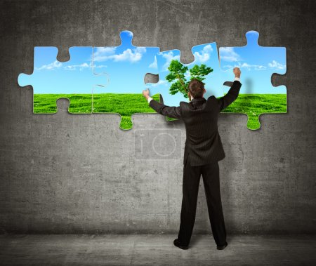 Photo for Businessman making a puzzle on the wall with picture of nature - Royalty Free Image