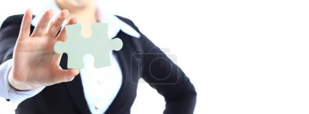 Cropped image of a woman in a business suit holding a single jigsaw piece