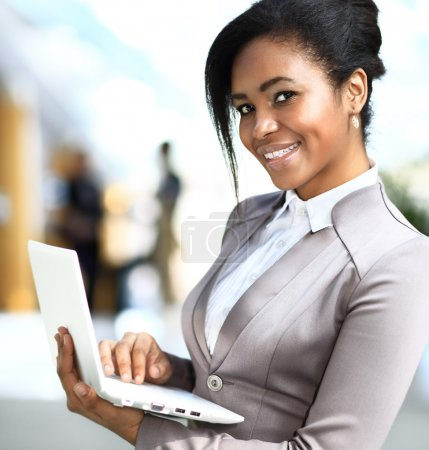 Business woman standing in foreground with laptop in her hands,