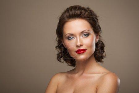 Photo pour Visage d'une belle jeune femme brune au maquillage lumineux et aux cheveux bouclés - image libre de droit