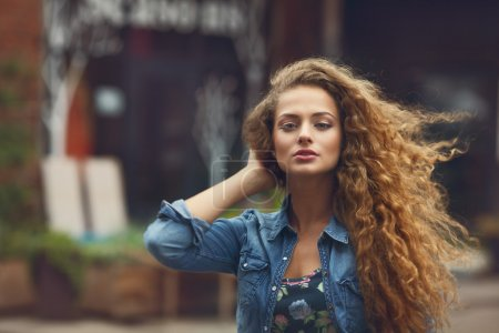 Beautiful young caucasian girl with curly hair outdoors