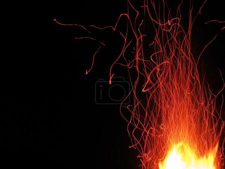 Photo pour Étincelles rouges volantes sur fond noir - image libre de droit