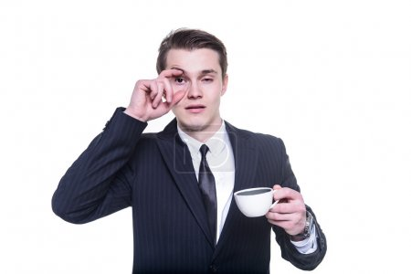 Businessman tired and falling asleep drinking a coffee