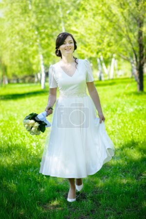 Beautiful happy bride walking on the green grass and holding bouquet of white roses.