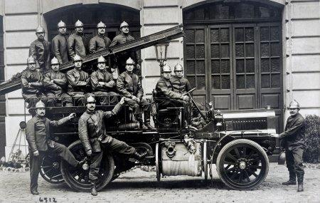Photo pour Vieille carte postale d'un groupe de pompiers sur un camion - image libre de droit