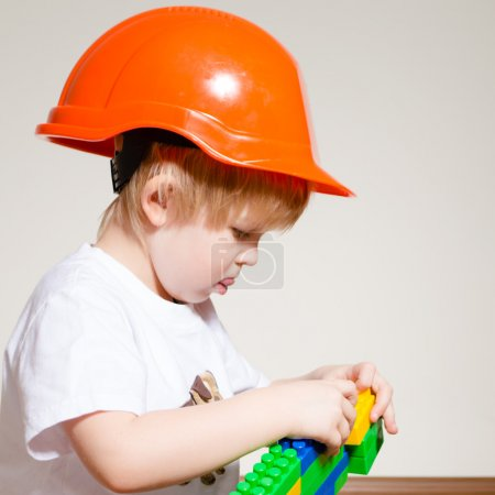 Little boy in builder helmet playing with constructor