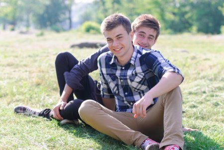 Two young men sitting together on green grass