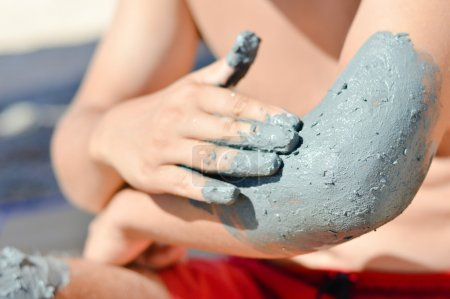 Man applying mineral blue mud on elbow