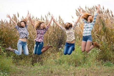 Photo pour Quatre amies adolescentes heureuses sautant haut dans le ciel bleu - image libre de droit