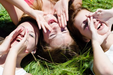 Three happy teen girls lying on green grass looking into sky and holding hands