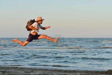 Young active man jumping high and running at seashore
