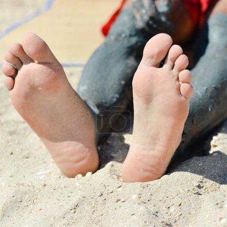 Foto de Joven om playa de arena aplicando barro azul mineral en el primer plano de la rodilla - Imagen libre de derechos