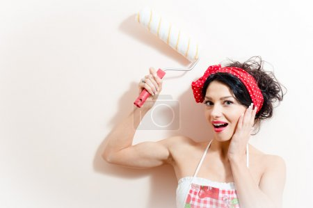 Funny charming young brunette woman beautiful pinup girl paint platen wall with roller happy smiling & looking at camera on white background closeup portrait