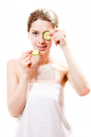 Girl standing with slices of cucumber