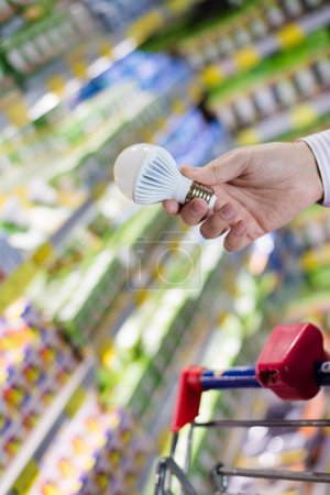 Choosing energy efficient lighting: closeup on male or female hand holding or selecting LED diode light bulb lamp in DIY department store with product display shelfs shop on the background