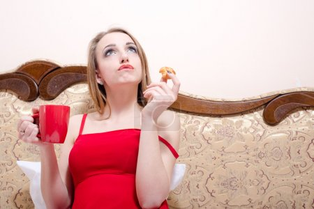 Photo for Sitting on bed or coach in red dress drinking tea and eating cake beautiful blonde young woman having fun looking up at copy space closeup portrait picture - Royalty Free Image