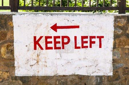 Photo pour Garder la gauche signe peint sur un mur en Inde - image libre de droit