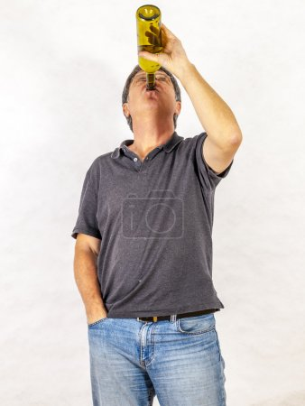 Mature man drinks alcohol out of a bottle...
