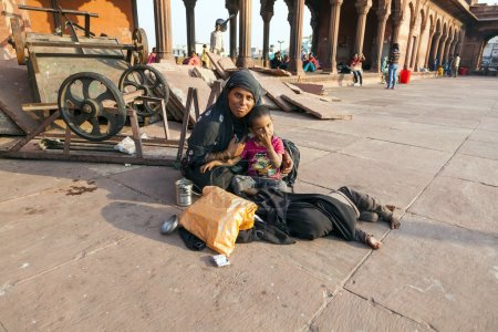 mother with childs rests on courtyard of Jama Masjid Mosque in D