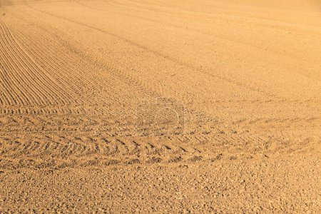 Freshly plowed field with marks of tire