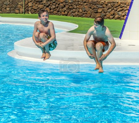 Two  friends jumping in the pool