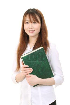 Photo pour Souriant jeune asiatique femme d'affaires tenant un livre - image libre de droit