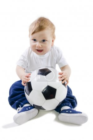 Baby sitting on floor with football ball