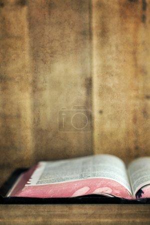 Photo pour Ancienne Bible, ouverte sur une étagère en bois. Avec des effets de grunge . - image libre de droit