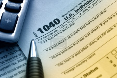 Photo for US tax form 1040 with pen and calculator. - Royalty Free Image