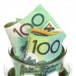 Australian money in jar, over white background. On...