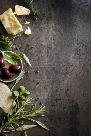 Photo for Food background with parmesan cheese, fresh herbs and olives, over dark slate. Lots of copy space. - Royalty Free Image