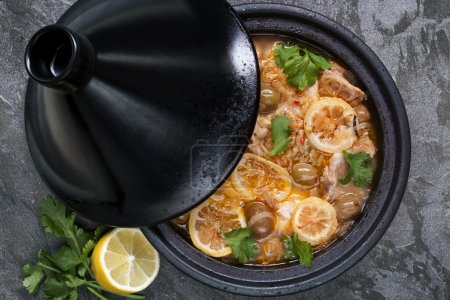 Photo for Chicken cooking in traditional tagine. With lemons, green olives and cilantro. - Royalty Free Image