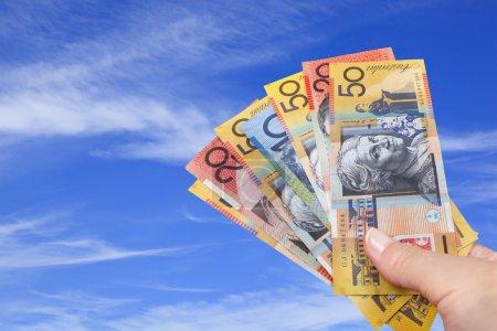 Handful of Australian money with blue sky backgrou...