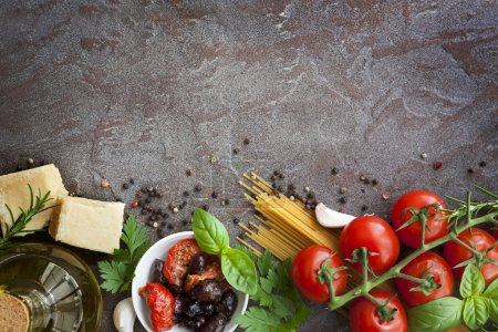 Photo for Italian food background, with vine tomatoes, basil, spaghetti, mushrooms, olives, parmesan, olive oil, garlic, peppercorns, rosemary, parsley and thyme. Slate background. - Royalty Free Image