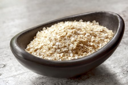 Photo for Quinoa flakes in small black bowl over rustic wood. - Royalty Free Image