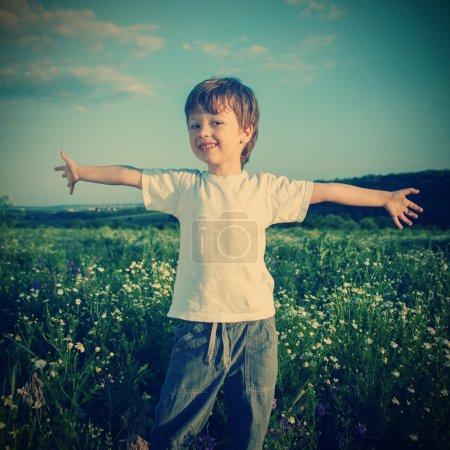Photo pour Heureux garçon sur vert champ - image libre de droit