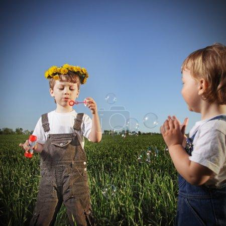 Photo pour Deux garçons jouent dans des bulles - image libre de droit