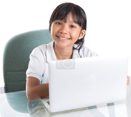 Photo pour Jeune asiatique malais écolière en uniforme scolaire avec un ordinateur portable - image libre de droit