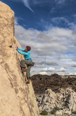 Female climber gripping the rock.