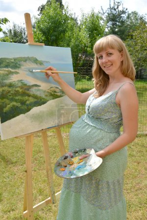 The young pregnant female artist draws a picture oil paints in t