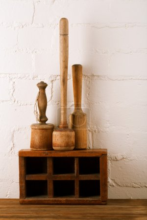 Retro kitchen utensils mashers on old wooden spice...