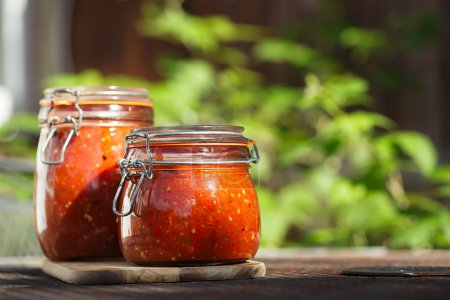 Photo for Jar of home made classic spicy Tomato, Chillie, garlic and Peper sauce salsa - Royalty Free Image