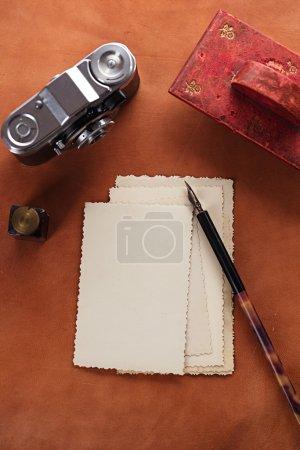 Photo pour Photos rétro, vintage encre, plume, buvard et caméra sur la vieille table en cuir - image libre de droit