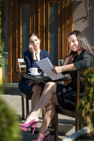 two business women sitting at a table in a cafe on the street
