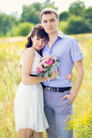 Photo pour Portrait d'un garçon et d'une fille avec un bouquet de debout contre les champs jaunes et les arbres verts - image libre de droit