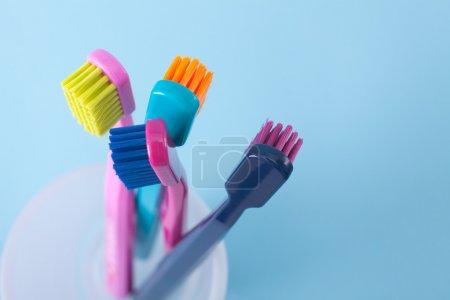 Photo pour Quatre brosses à dents - hygiène dentaire. Vue du dessus, sélectif centré sur le dessus de la brosse à dents droite, fond bleu . - image libre de droit