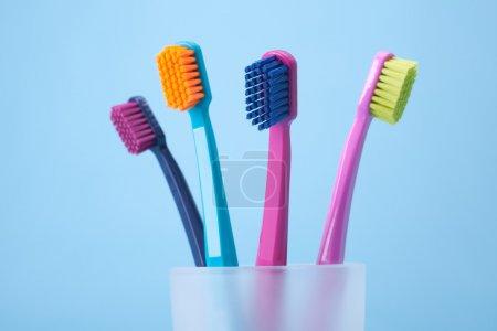 Photo pour Quatre brosses à dents - hygiène dentaire. Vue latérale, mise au point sélective sur la brosse à dents avant, fond bleu . - image libre de droit