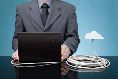 Photo pour Concept de cloud computing. L'homme envoie des données de l'ordinateur portable au nuage via un câble Ethernet - image libre de droit