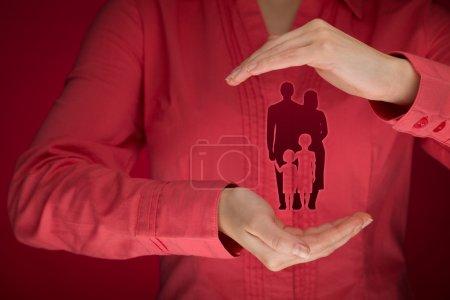 Photo pour Femme avec geste protecteur et silhouette représentant la jeune famille - image libre de droit